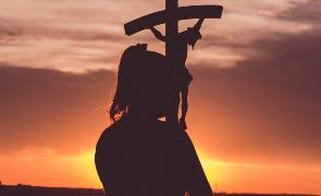 Chica lleva un crucifijo en alto al amanecer